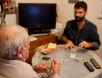 Un voluntario jugando a las cartas con una persona mayor